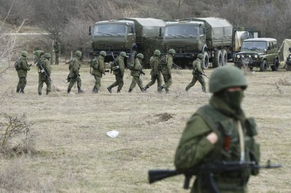 Reuters Military personnel, believed to be Russian servicemen, march outside the territory of a Ukrainian