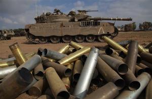 Cengkerang kosong berbaring di atas tanah di sebelah kereta kebal Merkava Israel di lokasi yang tidak ditentukan berhampiran sempadan Israel dengan Jalur Gaza.