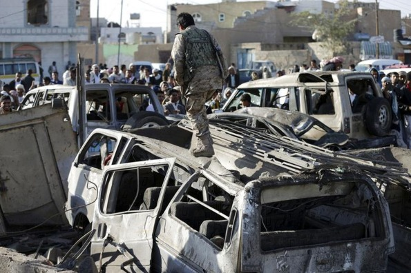 A Houthi fighter walks on a vehicle damaged by an air strike at a residential area near Sanaa Airport