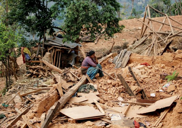 Woman sits on the rubble of her house at village following Saturday's earthquake in Sindhupalchowk