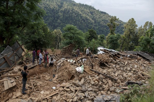 Villagers gather near a damaged house where three were killed by the earthquake at Jharibar Village, in Gorkha