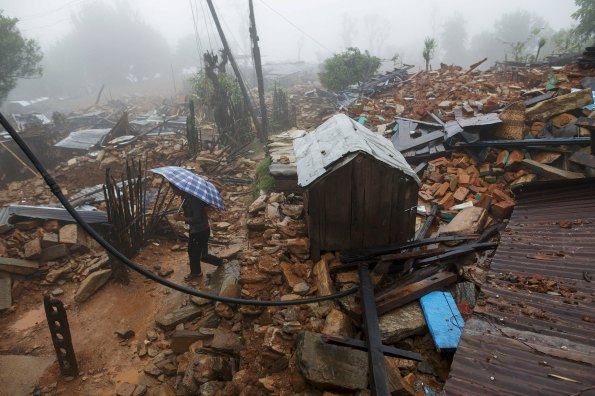 Man holds up a umbrella as he walks past a devastated area following Saturday's earthquake, at Paslang village in Gorkha