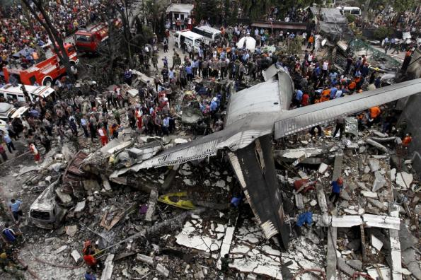 Security forces and rescue teams examine the wreckage of an Indonesian military C-130 Hercules transport plane after it crashed into a residential area in the North Sumatra city of Medan, Indonesia, June 30, 2015. At least 55 people were killed when a military transport plane crashed into a residential area shortly after take-off in northern Indonesia on Tuesday, but the toll looked set to rise after it emerged that more than 100 people had been on board. REUTERS/Roni Bintang