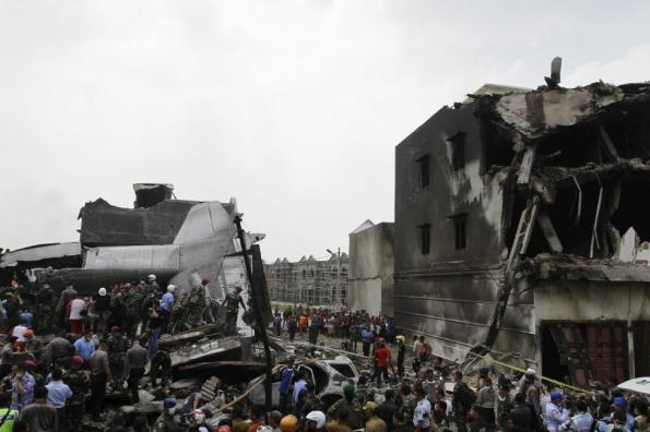 Security forces and rescue teams examine the wreckage of an Indonesian military C-130 Hercules transport plane after it crashed into a residential area in the North Sumatra city of Medan, Indonesia, June 30, 2015. REUTERS/Roni Bintang
