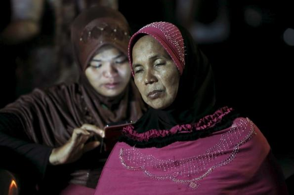 Family members sit outside Adam Malik hospital as they wait for the bodies of victims of an Indonesian military C-130 Hercules transport plane that crashed into a residential area in the North Sumatra city of Medan, Indonesia, June 30, 2015. REUTERS/Beawiharta