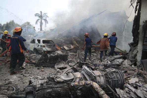 Firemen attempt to extinguish the fire surrounding the wreckage of an Indonesian military transport plane after it crashed in the North Sumatra city of Medan, Indonesia, June 30, 2015. REUTERS/Irsan Mulyadi/Antara Foto