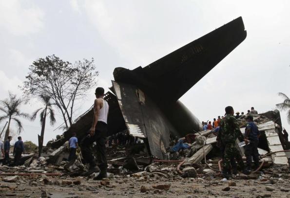 Security forces and rescue teams examine the the wreckage of an Indonesian military C-130 Hercules transport plane after it crashed into a residential area in the North Sumatra city of Medan, Indonesia, June 30, 2015. REUTERS/Roni Bintang