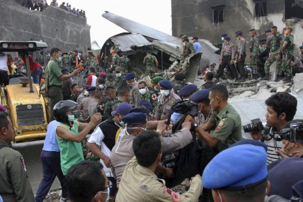 Security forces and rescue teams remove the bodies of victims from the wreckage of an Indonesian military C-130 Hercules transport plane after it crashed into a residential area in the North Sumatra city of Medan, Indonesia, June 30, 2015. REUTERS/Irsan Mulyadi/Antara Foto