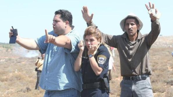 Striking photo of Palestinians shielding Israeli policewoman from stones thrown by settlers.