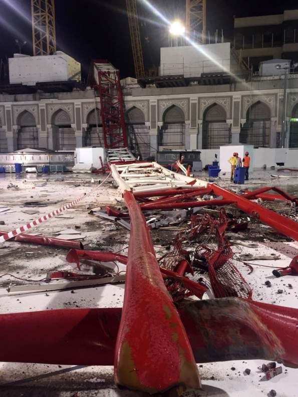 Saudi emergency teams stand next to a construction crane after it crashed into the Grand Mosque of Saudi Arabia's holy Muslim city of Mecca on September 11, 2015. A massive construction crane crashed into the Grand Mosque in stormy weather, killing at least 87 people and injuring 184, Saudi authorities said, less than a fortnight before the hajj pilgrimage starts. AFP PHOTO / STR