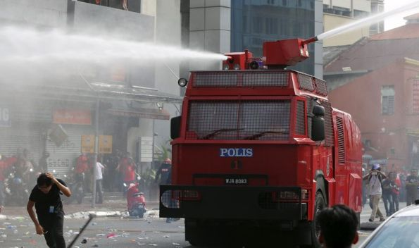 """A """"Red Shirt"""" demonstrator runs away from a water cannon used during a rally to celebrate Malaysia Day and to counter a massive protest held over two days last month that called for Prime Minister Najib Razak's resignation over a graft scandal, in Malaysia's capital city of Kuala Lumpur September 16, 2015. The Malaysian government warned the Malay organisers of a mass rally getting underway in Kuala Lumpur on Wednesday to avoid racial slurs and slogans that could raise tensions in the multi-ethnic Southeast Asian nation. REUTERS/Olivia Harris"""