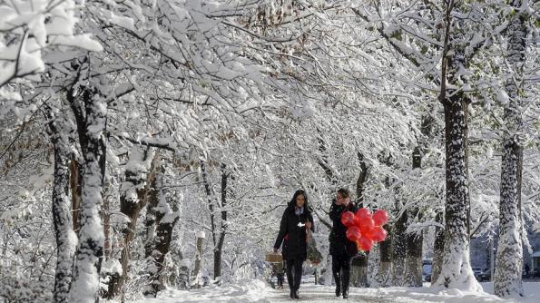 wanita berjalan di sepanjang diliputi salji lorong di Almaty, Kazakhstan. November 16, 2015. Photo: REUTERS / Shamil Zhumatov